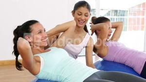 Trainer helping client do sit ups on exercise ball