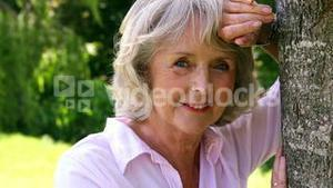 Retired woman leaning against tree smiling at camera