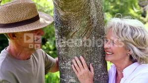 Retired couple leaning against tree smiling at each other