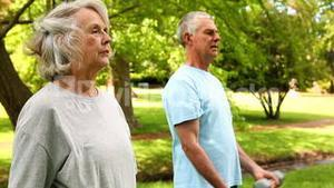 Retired couple lifting weights outside