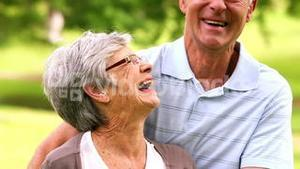 Affectionate senior couple in the park hugging