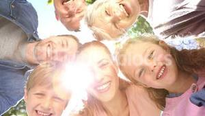 Extended family standing in the park together smiling down at camera