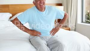 Senior man sitting on bed with a stomach ache