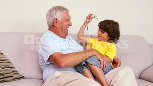 Senior man sitting on couch with his grandson