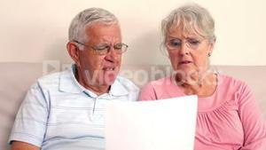Worried senior couple reading a document