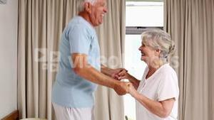 Senior couple jumping on the bed