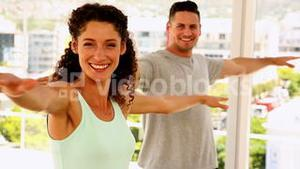 Happy fit couple smiling at the camera doing yoga