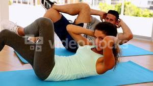 Happy fit couple doing sit ups together