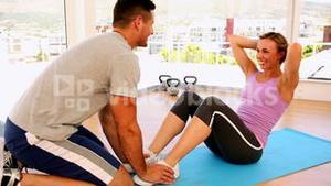 Happy fit woman doing sit ups with her trainer