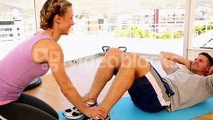 Happy fit man doing sit ups with his trainer