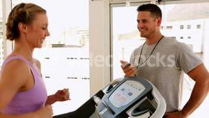 Fit woman running on treadmill with trainer timing her