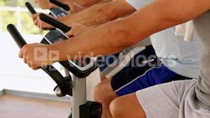 Three men working out on exercise bikes