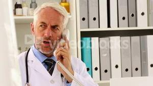 Doctor talking on the phone at his desk