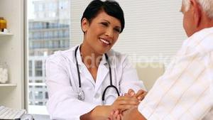 Doctor speaking with elderly patient and comforting him