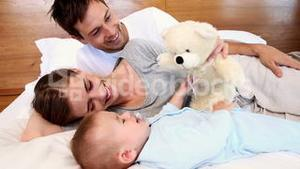 Happy parents lying on bed with baby son