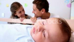 Happy parents watching over baby son in crib