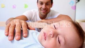 Happy father watching over baby son in crib
