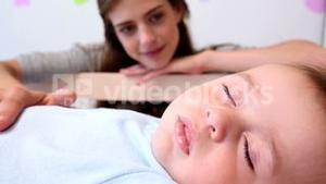 Happy mother watching over baby son in crib