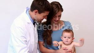 Pretty mother holding baby boy while pediatrician listens to his chest