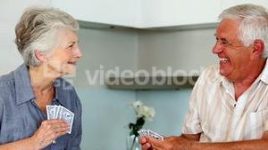 Senior couple playing cards at the counter