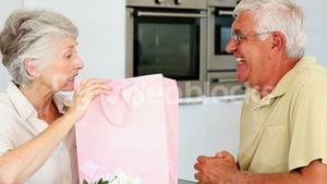 Senior man giving his partner a present in a pink bag