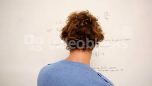 Confused student standing in front of whiteboard of math