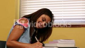 Pretty student studying at desk in classroom