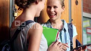 Classmates standing in hallway using tablet pc
