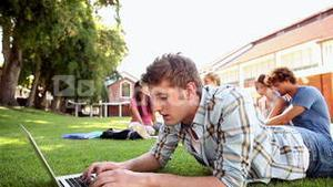 Student using laptop with classmates sitting behind on grass