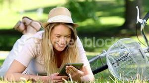 Pretty girl using tablet pc beside her bike in the park