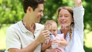 Happy parents with their baby girl in the park