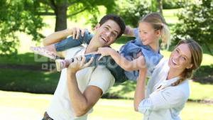 Happy parents with their little girl in the park