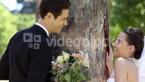 Happy newlyweds posing in the park beside a tree