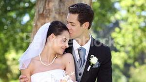 Happy newlyweds sitting in the park beside a tree