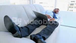 Businessman sleeping on couch with his laptop