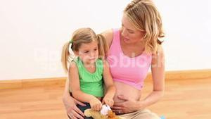 Blonde pregnant woman sitting with her little girl