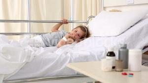 Little girl lying in hospital bed looking at medicine