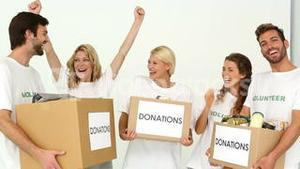 Team of volunteers holding donation boxes and cheering