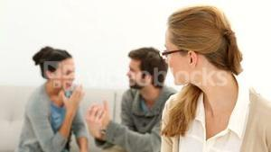 Young unhappy couple sitting on sofa behind therapist