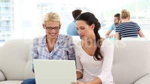 Creative partners using laptop on sofa with colleagues behind