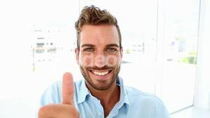 Businessman drinking coffee and giving thumbs up