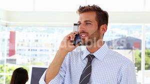 Man talking on phone while colleague works behind him