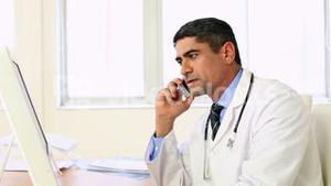 Doctor working at his desk talking on the phone
