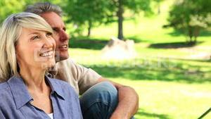 Happy couple sitting in the park