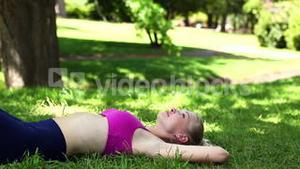Fit blonde lying on the grass