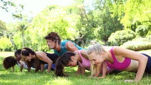 Fitness class doing push ups in the park
