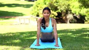 Fit asian girl doing yoga in the park