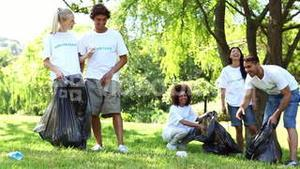 Happy volunteers picking up trash in the park