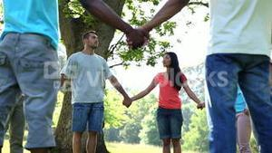 Young people holding hands in a circle