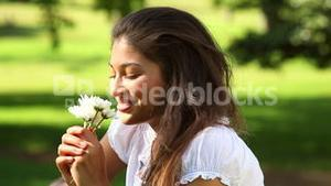 Pretty girl sitting on the grass smelling flowers